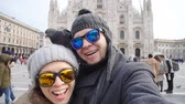 explorers : Happy tourists and pigeons taking a self portrait with phone in front of Duomo cathedral,Milan. Winter travel concept