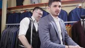 retailer : Man suit concept. Seller helps the buyer choose a suit in the clothing store
