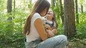 Family concept. Young happy mother hugging her daughter in the park