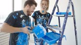 женат : Happy charming couple having fun and painting a room in their new house