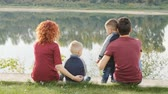quatro pessoas : Family and children concept. Young couple with two sons walking by the river