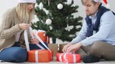 Concept of Christmas and happy New Year. Happy young couple opening a Christmas presents Dostupné videozáznamy