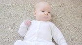 supine : Concept of children and parenthood. Cute Happy Baby is Lying on Carpet Stock Footage