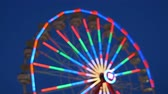 fairgrounds : The colorfully illuminated Gentle Giant Ferris Wheel (defocused) spins against the twilight sky during the 2014 New Jersey State Fair at the Sussex County Fairgrounds in Augusta, New Jersey.