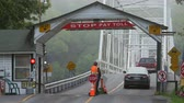 lacuna : DINGMANS FERRY, PA - AUGUST 5: Commuters stop and pay the toll before crossing Dingmans Ferry Bridge on August 5, 2014 in Dingmans Ferry, Pennsylvania. The bridge crossed the Delaware River from Pennsylvania to New Jersey. Stock Footage