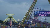 fairgrounds : AUGUSTA, NJ - AUGUST 5: (Time-lapse) Colorfully illuminated carnival rides including the Yo-Yo, Pharoahs Fury and the Gentle Giant Ferris Wheel spin at twilight during the New Jersey State Fair on August 5, 2014 at the Sussex County Fairgrounds in August