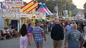 karnaval : AUGUSTA, NJ - AUGUST 6: (Slow Motion) People walk on the midway during the New Jersey State Fair on August 6, 2014 at the Sussex County Fairgrounds in Augusta, New Jersey. Stok Video