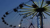 fairgrounds : AUGUSTA, NJ - AUGUST 6: The colorfully illuminated Yo-Yo spins in front of the Gentle Giant Ferris Wheel at twilight sky during the New Jersey State Fair on August 6, 2014 at the Sussex County Fairgrounds in Augusta, New Jersey.