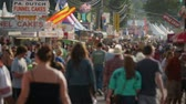 fairgrounds : AUGUSTA, NJ - AUGUST 6: (Slow Motion) People walk on the midway during the New Jersey State Fair on August 6, 2014 at the Sussex County Fairgrounds in Augusta, New Jersey. Stock Footage