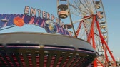 fairgrounds : AUGUSTA, NJ - AUGUST 7: The colorfully illuminated Enterprise spins in front of the Gentle Giant Ferris Wheel during the New Jersey State Fair on August 7, 2014 at the Sussex County Fairgrounds in Augusta, New Jersey. Stock Footage
