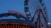 fairgrounds : AUGUSTA, NJ - AUGUST 7: The colorfully illuminated Enterprise spins in front of the Gentle Giant Ferris Wheel at twilight during the New Jersey State Fair on August 7, 2014 at the Sussex County Fairgrounds in Augusta, New Jersey. Stock Footage
