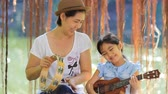 eğitim : Asian mother playing ukulele for her daughter in park