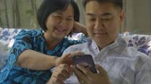 技術 : Asian senior woman and Asian man using smart phone together