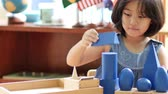 little : Little Asian girl stacking montessori blocks