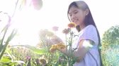 everlasting : Happy Asian girl walking in the flower field with sunlight, Slow motion shot