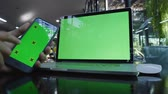 rolování : Close up man hands touching smart phone and using laptop with green screen