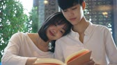 平等 : Close up Young Asian couple reading a book together
