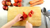болгарский : Top view chef cuts bulgarian pepper into slices on a cutting board