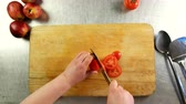 dilimleme : Top view cook cuts tomato into slices on a cutting board