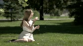varinha : Girl sits on the grass and blowing bubbles