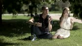 varinha : Girl and boy blow the soap bubbles while sitting on the grass