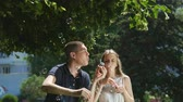 varinha : Young woman and young man blow the soap bubbles while sitting on the grass Vídeos