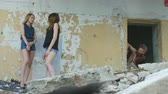 terrível : Girls communicate and a maniac looks out from the doorway of old building