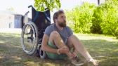 гандикап : Young disable man trying to sit down in a wheelchair Стоковые видеозаписи