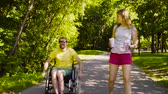 restringido : Young disable man with his wife on a walk in the park