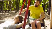 restringido : Woman is lying on a swing and a man is pushing a swing Stock Footage