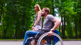 restringido : Young disable man walking in the park with his wife