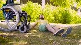 restringido : Happy young disable man sitting on the grass in the park Stock Footage