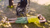 restringido : Young disable man is relaxing on the ground in the park Stock Footage