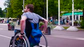 restringido : Young disable man walking in the park in wheelchair