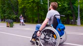 inválido : Young disable man walking in the park in wheelchair
