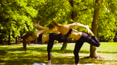 pratica : Yoga. Due donna attraente facendo yoga exersices nel parco