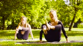 stretches : Yoga. Two attractive woman doing yoga exersices in the park