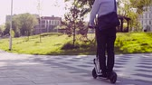 lambreta : A man in a business suit riding a kick scooter Stock Footage