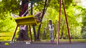 freizeitpark : Two girls are sitting on a swing, and the third is pushing them Videos