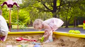 複雑な : A little girl sitting in a sandbox is picking up sand