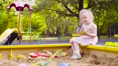 dětské hřiště : A little girl sitting in a sandbox is picking up sand