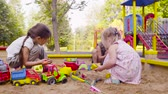 aire de jeux : Three girls sitting in a sandbox and picking up sand