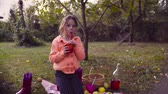 sroka : Picnic in the garden. A girl sitting on grass and drinking compot Wideo