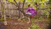 いたずらな : Little girl sitting on a tree and eating apple 動画素材