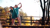 Young happy couple dancing on the wooden bridge