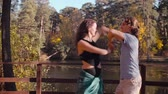 Couple dancing on the wooden bridge in autumn
