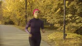 follows : Young sportswoman running along the road Stock Footage