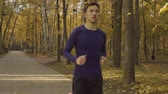 portrait shot : Young man running along the road in the park Stock Footage
