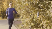 follows : Young man running along the road in the park Stock Footage