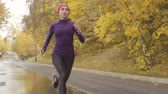 dürtmek : Young sportswoman running along the road Stok Video